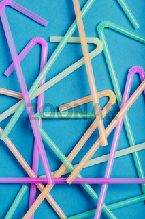 Heap of plastic drink straws scattered over blue background