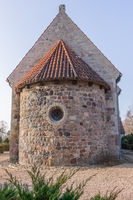 A round apse of a medieval stone churh, with a round window at the east, Tveje Merlose, Denmark