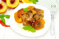 Turkey with peaches in plate on wooden board
