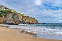 Shore and ocean by a rocky cliff against cloudy sky in Laguna Beach California