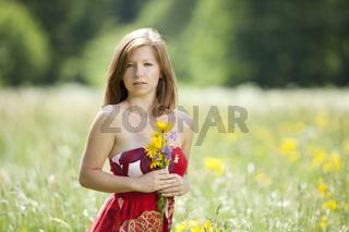 Junge Frau steht mit Blumen in der Hand in einer Wiese