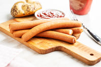 Fresh frankfurter sausages with bun and ketchup.