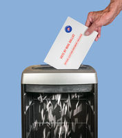 Absentee ballot of vote by mail envelope being shredded in an office shredder