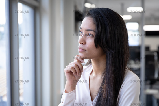 Thoughtful businesswoman looking out of a window while her hand on her chin at modern office