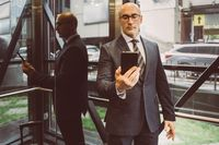 Thoughtful businessman in suit reading information in smartphone hold in it in front of him standing next to a window with a busy street view. Focused business man face with smartphone