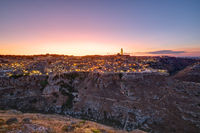 The beautiful old town of Matera and the canyon of the Gravina river after sunset