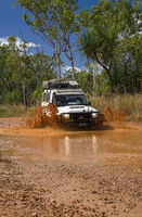 Western Australia – Flooded Outback gravel road with 4WD car crossing the waterhole with splashing muddy water at the savanna