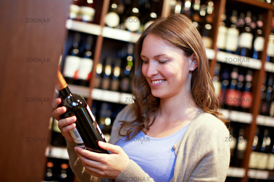 Frau betrachtet Weinflasche