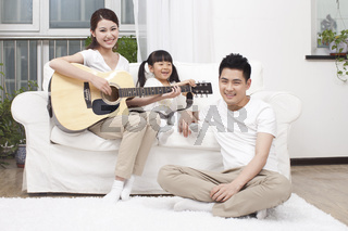 Young family playing guitar in living room