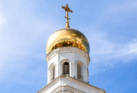 Golden dome with religious cross of bell tower