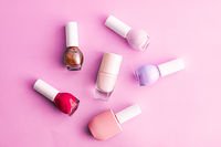 Nail polish bottles on pink background, beauty brand