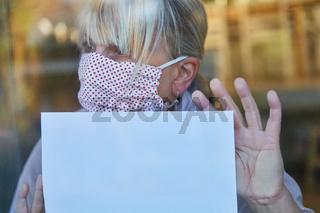 Seniorin mit Mundschutz hält leeren Zettel an Fenster in Coronavirus Quarantäne