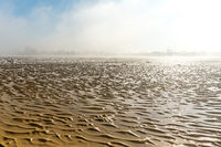 landscape of fog lifting over an endless wadden sea beach at low tide