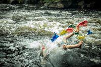 Spiritual man swims by tibetan flags