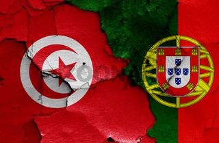 flags of Tunisia and Portugal painted on cracked wall