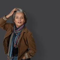 Sexy mid aged woman touches her graying hair and looks at the camera. Studio portrait of fashion lady in casual