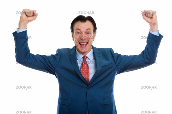 Studio shot of mature happy businessman looking excited while getting good news