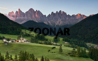 Village of Santa Magdalena and church on the Italian mountains Dolomites Alps at sunrise