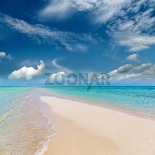 white sandy sea spit beach leading into ocean