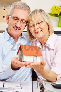 Paar Senioren hält Haus auf den Händen