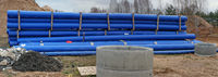 Long blue plastic pipes  for the restoration of the old decayed sewage system in the European forest