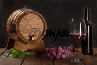 A glass of red wine with a bottle, a wine barrel, grapes, and vine leaves, side view on a dark rustic background, low key photo