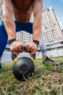 Sportive guy training with kettlebell on the background of a tall building.