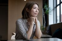 Pensive asian woman looking out of window in office cafeteria