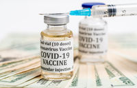 Close up of hypodermic syringe on bottle of Covid-19 vaccine with cash