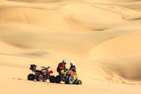 Quadbike driving people having breakdown and stuck in sand.