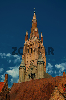 Brick church steeple with roofs in Bruges