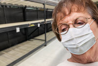 Senior Adult Woman In Medical Face Mask Walking Down Empty Aisle of Grocery Store