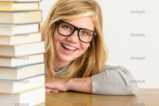 Cheerful student teenager look from behind books