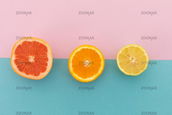 Grapefruit, orange and lemon halves on pink and blue background