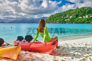 Woman sitting on kayak at beach, Seychelles, Mahe