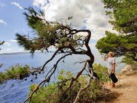 Young active feamle tourist taking a break, drinking water, wearing small backpack while walking on coastal path among pine trees looking for remote cove to swim alone in peace on seaside in Croatia
