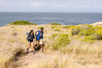 Fit african american couple wearing backpacks nordic walking on coast