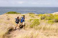 Fit african american couple wearing backpacks nordic walking on coast