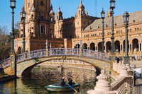 Tourists go on row boat around the water of Guadalquivir river in Plaza de Espana. Seville, Spain