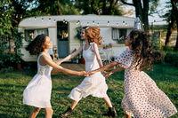 Happy beautiful women dancing in circle during a picnic