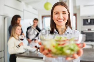 Junge lächelnde Frau in Küche mit einer Schüssel Salat