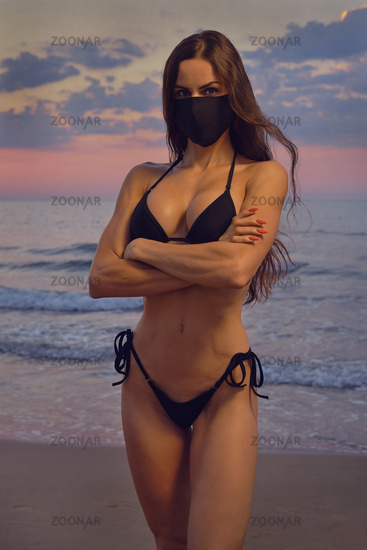Sensual young lady pretty girl wear black color cloth mask and bikini pose on nature at sunrise near sea. Concept covid-19 outbreak. Obligatory compulsory use face masks outdoors. Fashion and beauty