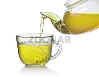 Tea pouring from teapot into glass cup