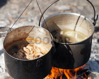 Cooking in two sooty old pots on bonfire at sunny summer day