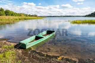 Old wooden fishing boat on the lake