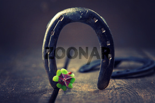 Horseshoe with lucky clover on a wooden background