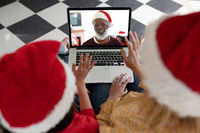 Rear view of woman and daughter in santa hats waving while having a videocall with senior man in san