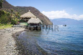 Jetty hut with straw roof at the coast of lake Atitlan with passing by speed boat at Santa Cruz La Laguna, Guatemala