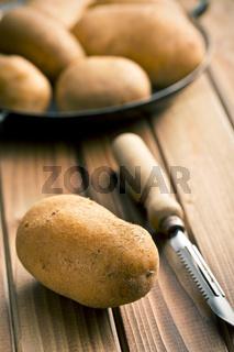 wooden peeler and potatoes