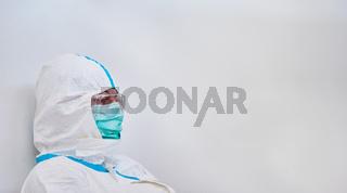 Arzt in Schutzkleidung ist nachdenklich in Pause während Coronavirus Pandemie